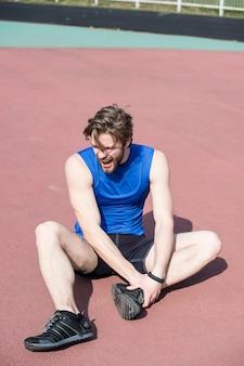 Corridore ferito, uomo barbuto o ragazzo con corpo atletico sulla pista da corsa, sensazione di dolore alla gamba rotta soleggiata all'aperto in abbigliamento sportivo blu. attività estiva, sport. stile di vita sano e allenamento. trauma sportivo