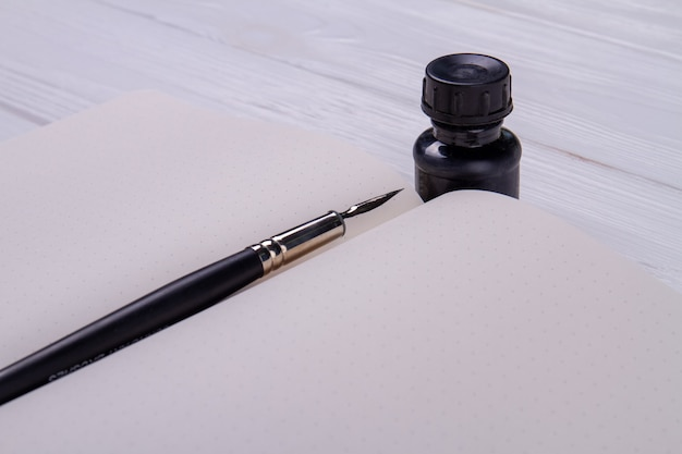 Penna a inchiostro sul quaderno vuoto.