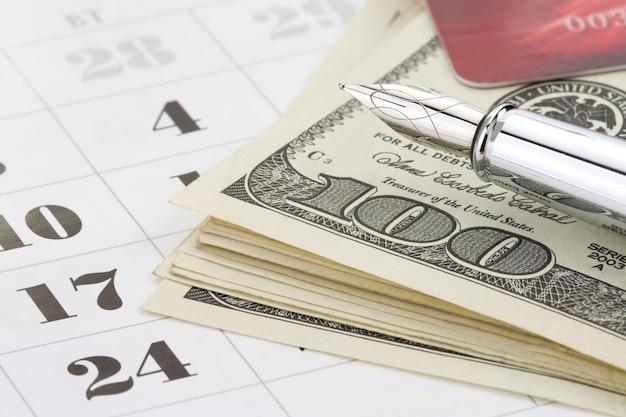Penna a inchiostro e soldi del dollaro sul calendario