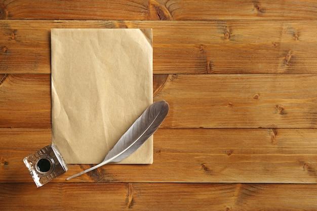 Calamaio con piuma e foglio di carta su legno