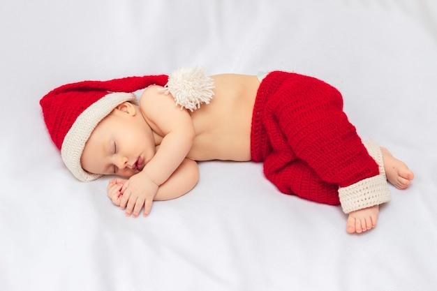 Bambino innocente che indossa cappello e pantaloni da elfo natalizio rosso lavorato a mano all'uncinetto, dormendo su una coperta di pile bianca