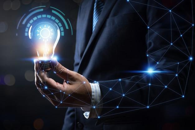 Innovazione ed energia del pensiero creativo, uomo d'affari che tiene lampadina che emette luce e illuminazione con collegamento al corpo umano e alla vita di potere