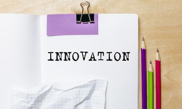 Testo di innovazione scritto su una carta con le matite sulla scrivania in ufficio