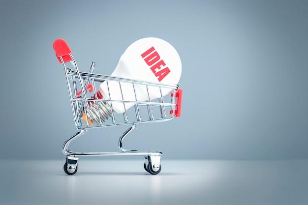 Idea innovativa moderna ed elegante con lampadina nel carrello del negozio.
