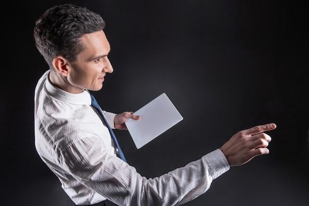 Tablet innovativo. vista dall'alto di un uomo piacevole positivo felice che sorride e che tiene un tablet innovativo mentre si utilizza la tecnologia moderna