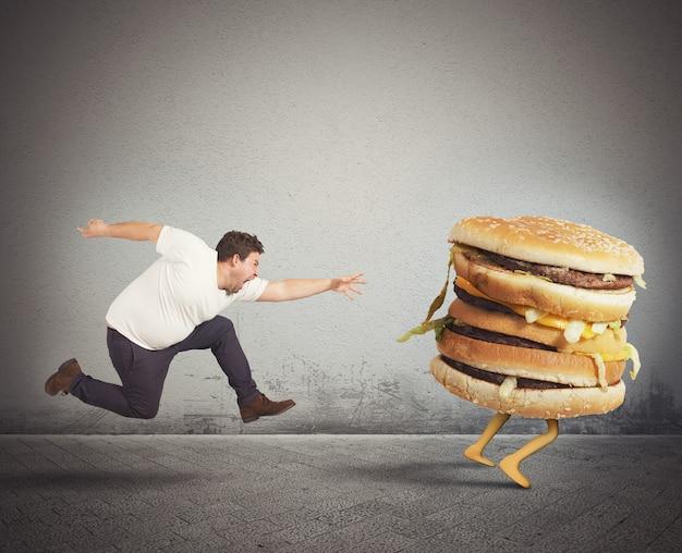 L'uomo grasso insaziabile corre per prendere un panino