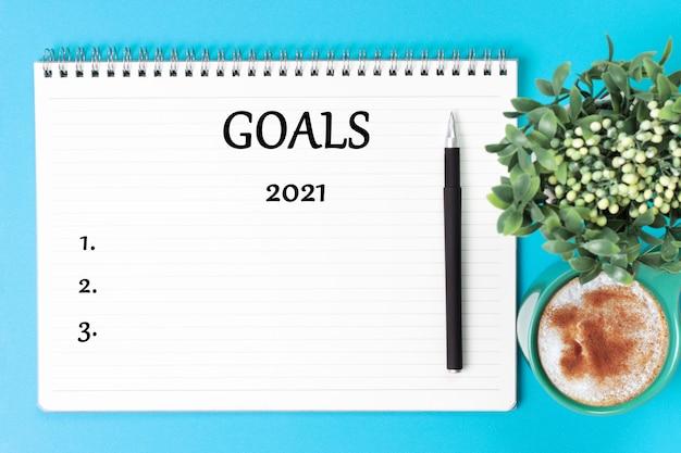 Iscrizione obiettivo 2021 in organizer bianco e pianta verde su sfondo blu
