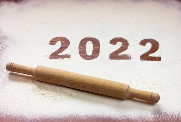 L'iscrizione 2022 è scritta sulla farina su un tavolo di legno con un mattarello accanto. concetto di nuovo anno.