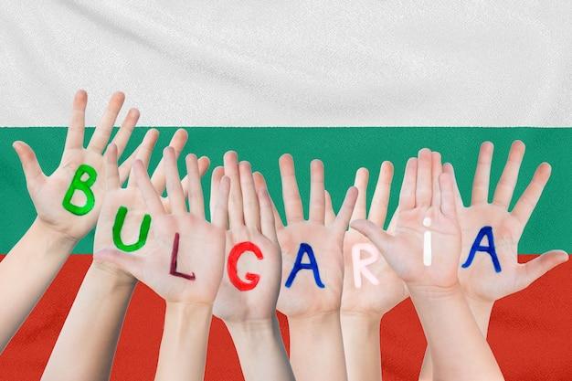 Iscrizione bulgaria sulle mani dei bambini contro la superficie di una bandiera sventolante della bulgaria