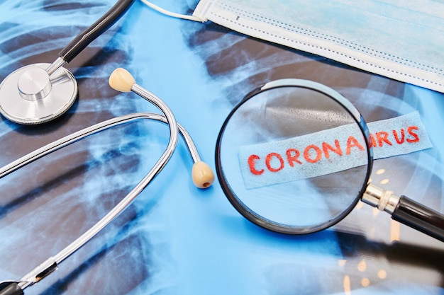 Iscrizione coronavirus attraverso una lente d'ingrandimento su sfondo di stetoscopio, mascherina medica e radiografia del polmone. avvicinamento