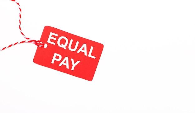 La scritta equal pay su un cartellino del prezzo rosso su sfondo chiaro. concetto di pubblicità. copia spazio