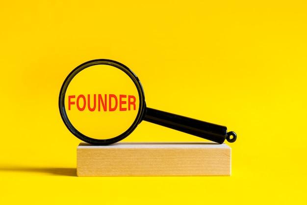 L'iscrizione fondatore tramite lente di ingrandimento su sfondo giallo. la lente d'ingrandimento è montata su un supporto di legno su un tavolo