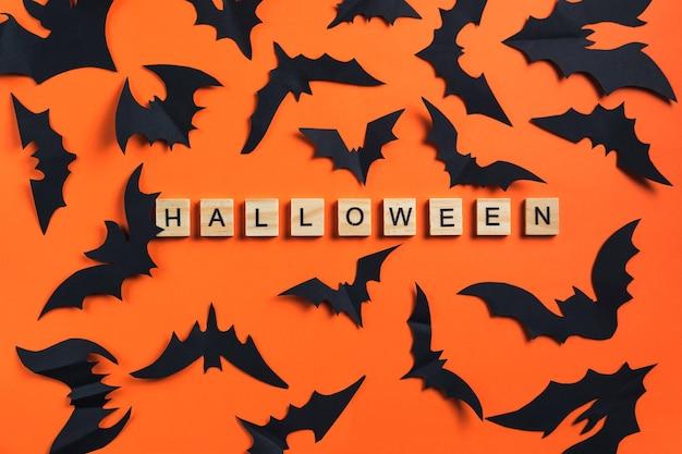 L'iscrizione da cubi di legno e pipistrelli tagliati da carta nera su uno sfondo arancione halloween