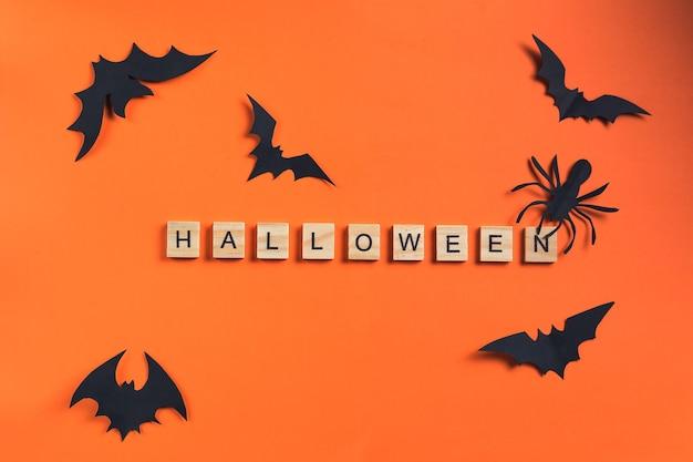 L'iscrizione da cubi di legno e pipistrelli tagliati da carta nera su uno sfondo arancione