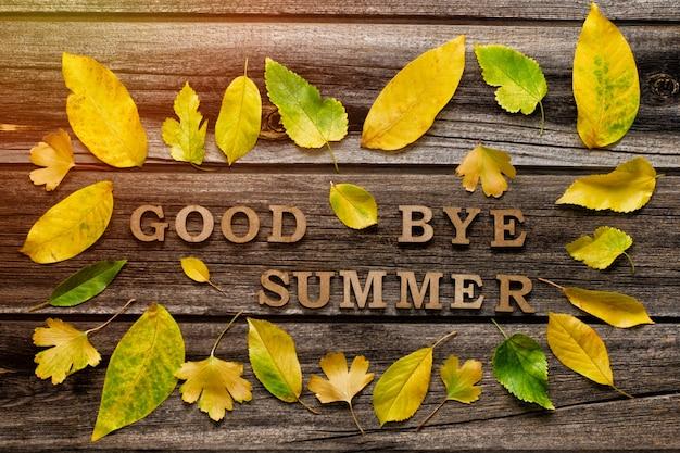 Iscrizione arrivederci estate su uno sfondo di legno, cornice di foglie gialle