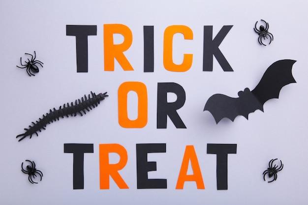 Iscrizione halloween con i pipistrelli di carta con i ragni su fondo grigio. halloween