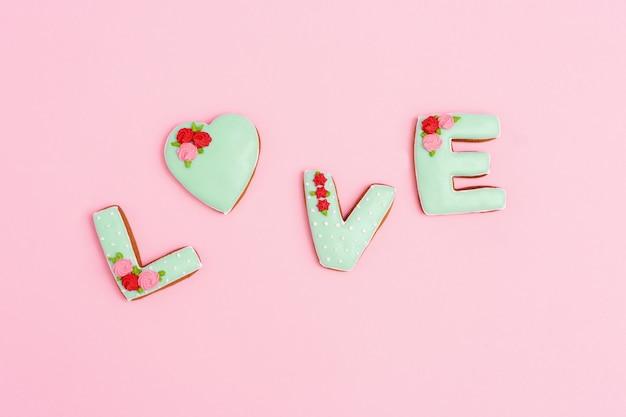 Amore dell'iscrizione dai biscotti casalinghi con glassa verde su colore pastello rosa. concetto di amore romantico. san valentino vista dall'alto.