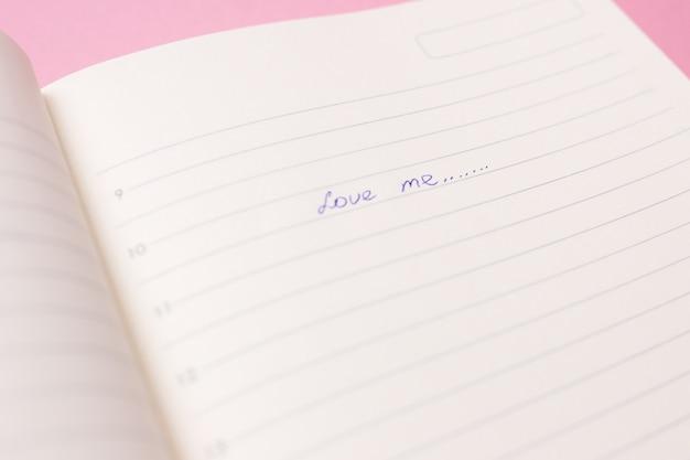L'iscrizione mi ama in un primo piano del diario su uno sfondo rosa.