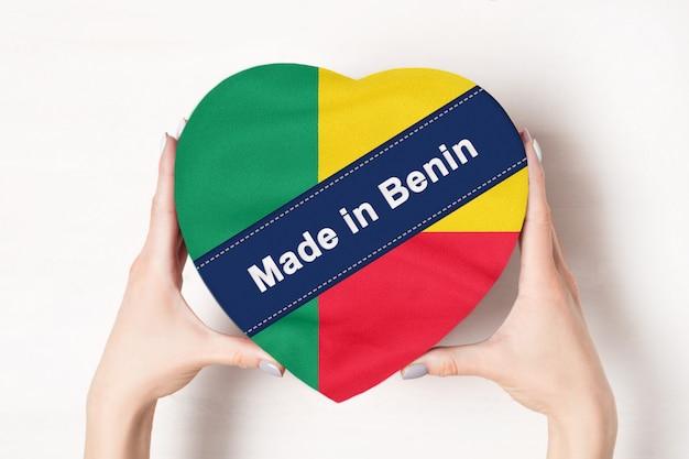 Iscrizione fatta in benin la bandiera del benin. mani femminili che tengono una scatola a forma di cuore.