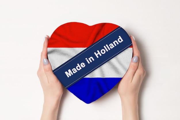 Iscrizione realizzata in olanda la bandiera dell'olanda. mani femminili che tengono una scatola a forma di cuore. muro bianco.