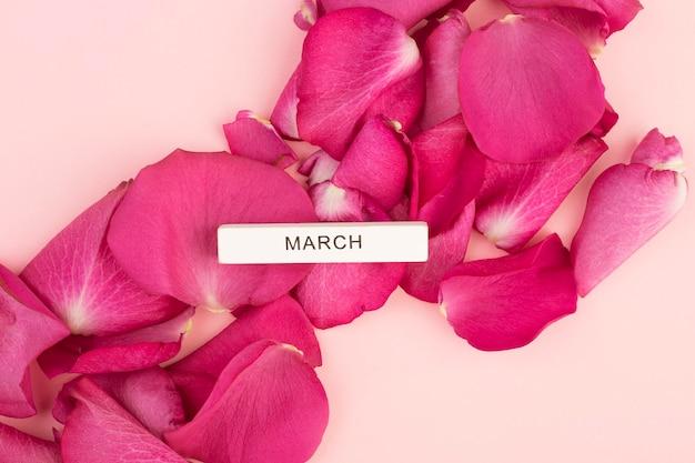 La scritta marzo su uno sfondo di petali di rosa