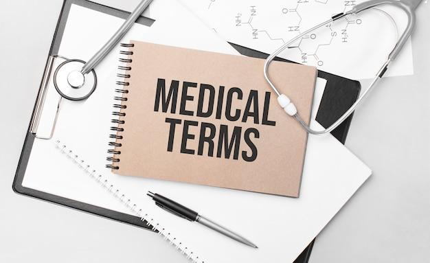 Iscrizione termini medici. vista dall'alto del tavolo con stetoscopio, penna e documenti medici.