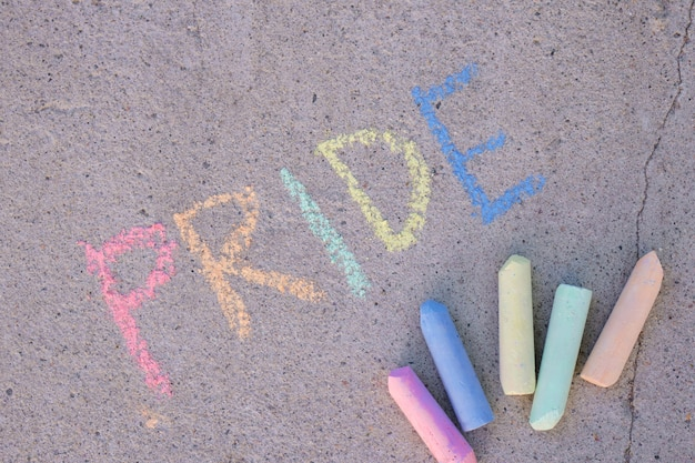 Iscrizione orgoglio con gesso sull'asfalto, vista dall'alto del concetto del mese dell'orgoglio