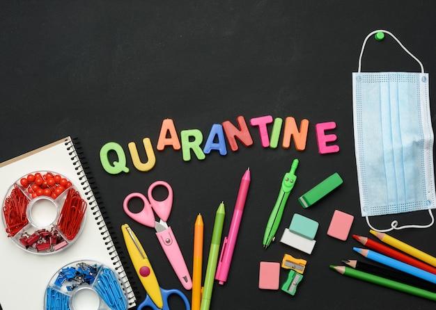 Quarantena di iscrizione da lettere in plastica multicolore e materiale scolastico sulla lavagna nera, concetto di chiusura delle scuole durante una pandemia