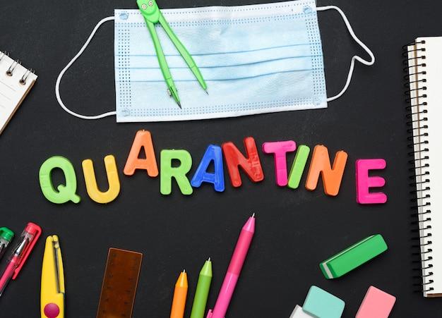 Quarantena di iscrizione da lettere di plastica multicolore e materiale scolastico sulla lavagna nera