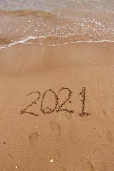 Iscrizione sul simbolo della sabbia sulla costa che si affaccia sul mare vacanze estive nella nuova stagione