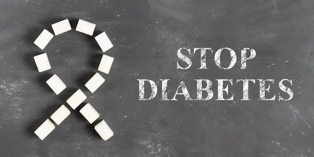 La scritta stop diabete in gesso su una lavagna grigia con un nastro di zucchero a grumi