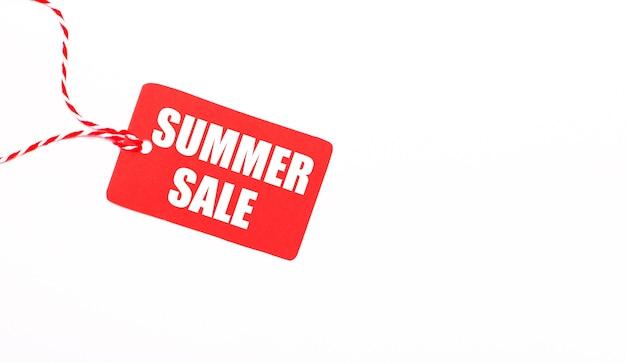La scritta summer sale su un cartellino del prezzo rosso su sfondo chiaro. concetto di pubblicità. copia spazio