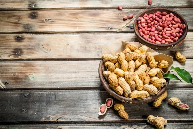 Inshell le arachidi e sbucciate nelle ciotole. su uno sfondo di legno.