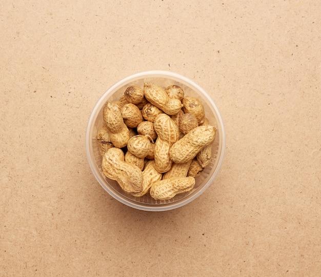 Arachidi inshell in una ciotola di plastica trasparente
