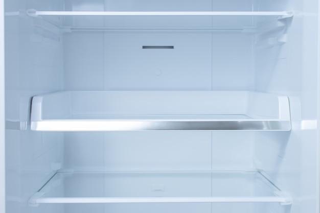 All'interno del frigorifero pulito e vuoto con ripiani.