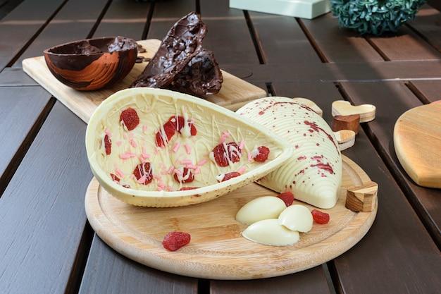 All'interno di un uovo di pasqua di cioccolato bianco con fragole candite su un piatto di legno. uovo di pasqua di cioccolato fondente con mandorle croccanti vista dall'alto foto verticale