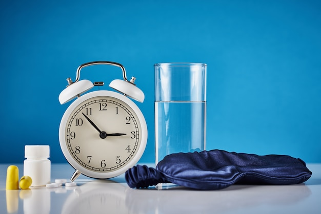 Problema di insonnia e concetto di disturbi del sonno. sveglia, bicchiere d'acqua, tappi per le orecchie e pillole su fondo blu