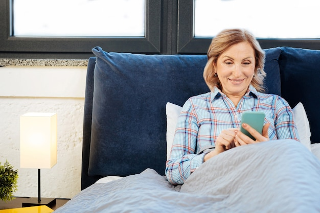 Ispezione dello smartphone. donna adulta concentrata che si appoggia sul suo letto e controlla i social media durante la solita routine mattutina