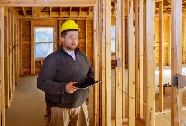 Ispettore che controlla costruzione durante la costruzione della casa sul pc della compressa con il cappello duro