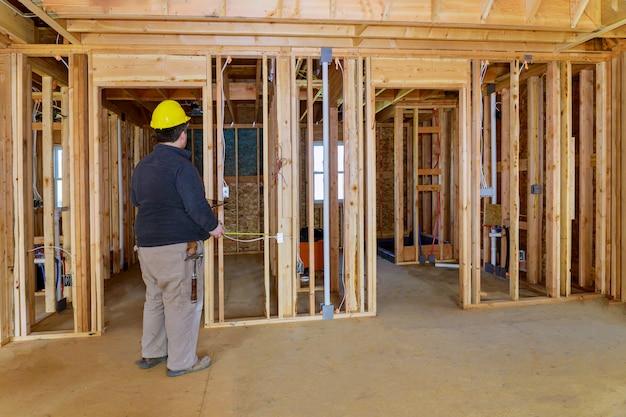 Ispettore che controlla la costruzione con il cappello duro sulla tenuta della casa del pc della compressa per vedere se il lavoro fatto correttamente