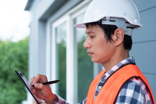 L'ispettore o l'ingegnere sta controllando la struttura dell'edificio e le specifiche del tetto della casa. al termine della ristrutturazione