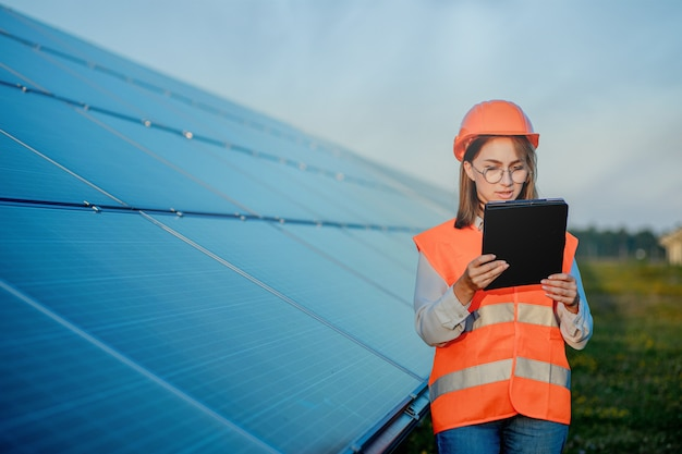 Ispettore ingegnere donna che tiene tavoletta digitale lavorando in pannelli solari power farm, parco di celle fotovoltaiche, concetto di energia verde.