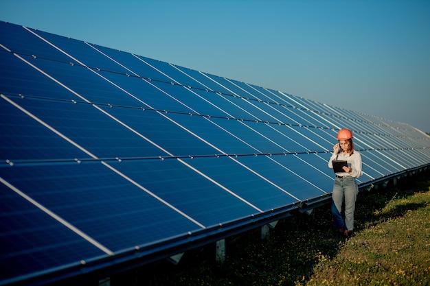 Donna dell'ingegnere ispettore che tiene la compressa digitale che lavora nella centrale elettrica dei pannelli solari