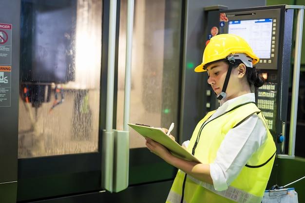 Ispettore che scrive la lista di controllo della nota sul blocco note per il risultato produttivo dell'acqua di raffreddamento elettrica della fabbrica