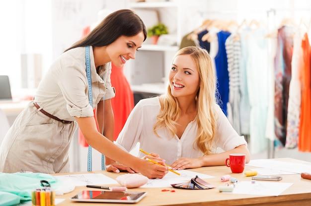 L'ispirazione arriva più velocemente quando siamo insieme. due giovani donne allegre che lavorano insieme nel loro laboratorio di moda