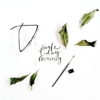 Citazione ispiratrice make today amazing scritta in stile calligrafico su carta con foglia verde e occhiali su sfondo bianco. lay piatto