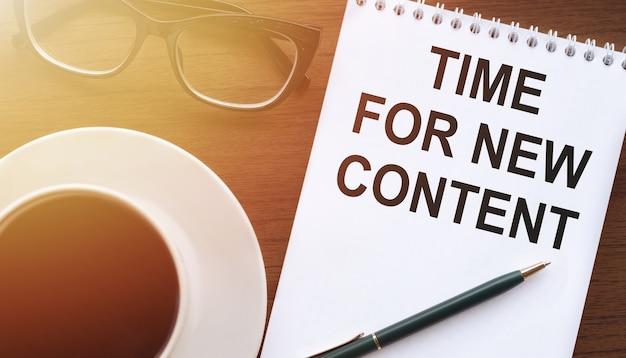 Testo di citazione ispiratrice sul blocco note - tempo per nuovi contenuti, sul tavolo con caffè e bicchieri.