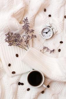 Natura morta ispiratrice - sveglia, tazza di caffè e fiori secchi su un accogliente maglione bianco. tempo di riposo e relax. vista dall'alto e verticale