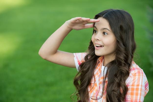 Ispirata ragazza carina con lunghi capelli ondulati guarda a distanza tenendo la mano sull'erba verde della fronte soleggiata estate all'aperto, futuro.
