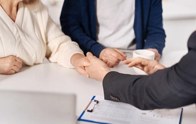 Ispirando fiducia. sincero fiducioso coppia di anziani seduti a casa e la conclusione di un accordo con l'agente immobiliare mentre si stringono la mano